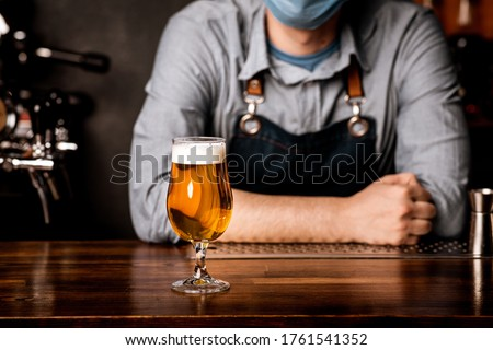 Quarantine, nightlife and pub. Bartender in protective mask leans on bar counter on which stands glass of light beer with foam, cropped #1761541352