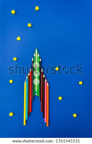 Space rocket made of colour pencils on blue cardboard is decorated with wooden stars and paper confetti in the form of portholes. Concept of children's creativity and schooling. Vertical, copy space