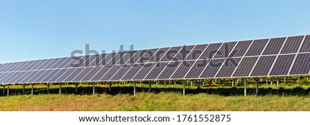 Solar photovoltaic panels on green grass meadow, clear sky above, wide banner photo