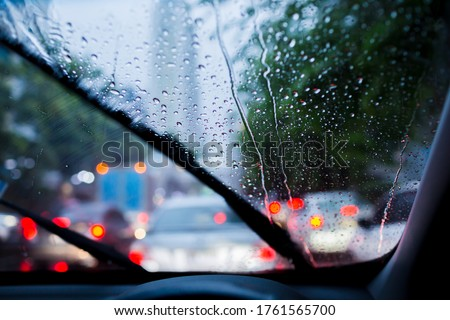 Selective focus to rain droplet with motion blurry wiper on windshield. Motion blurry windshield wipers from inside of car, season rain. Royalty-Free Stock Photo #1761565700