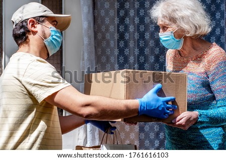 Young male volunteer in mask gives an elderly woman boxes with food near her house. Son helps a single elderly mother. Family support, caring. Quarantined, isolated. Coronavirus covid-19. Donation Royalty-Free Stock Photo #1761616103