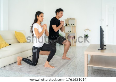 Young Asian couple doing squats training together and looking TV at home, man and woman working out together standing in living room, fit pair performing fitness exercise with partner. Royalty-Free Stock Photo #1761621014