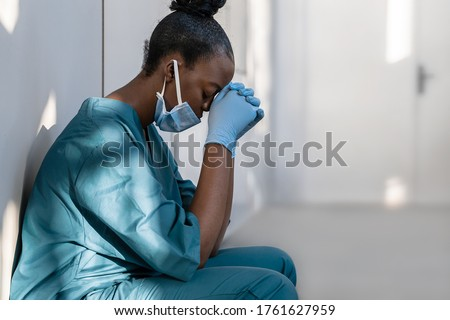 Tired depressed female african scrub nurse wears face mask blue uniform gloves sits on hospital floor. Exhausted sad black doctor feels burnout stress of corona virus frontline protection pray at work #1761627959