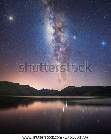 Starry night with the bright Milky Way, Mars, Saturn and Jupiter and over mountains.
