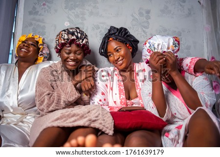 Four beautiful African girlfriends wearing hair bonnet and robes,laughing and having fun on vacation holidays,treatment at spa - Black Pretty bridesmaids indoors looking cheerful Royalty-Free Stock Photo #1761639179