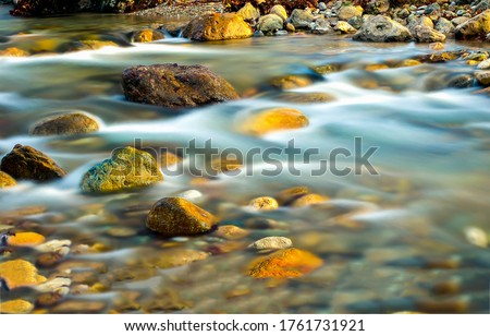 River stream water flow view. Water stnes in river stream. stream water motion Royalty-Free Stock Photo #1761731921