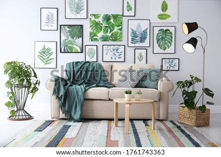 Beautiful artworks and comfortable couch in stylish room. Interior design Royalty-Free Stock Photo #1761743363