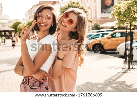 Two young beautiful smiling hipster girls in trendy summer clothes.Sexy carefree women posing on the street background in sunglasses. Positive models having fun and hugging.They going crazy