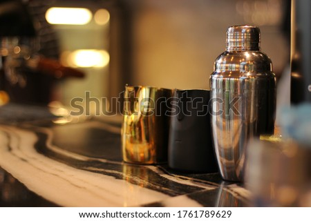 Bar Accessories: Cobbler Shaker, Manhattan Cocktail Shaker, Traditional Shaker made from stainless steel with black and gold jigger on Counter Bar  low light background. #1761789629
