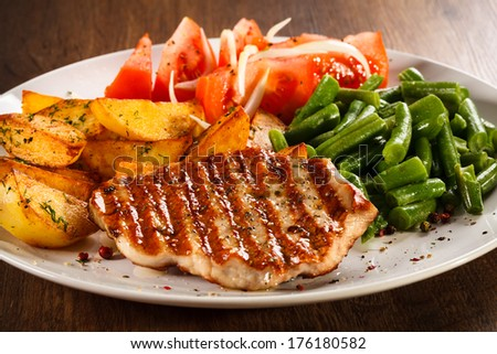Grilled steaks, baked potatoes and vegetables  #176180582