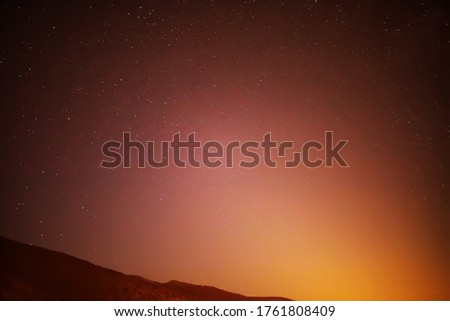 Starry sky at night in the Tyrolean Alps. Moonrise On a colorful sky, stars and comets. Orange #1761808409