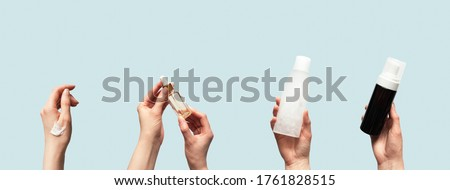 Hands up holding beauty cosmetic products isolated on blue background horizontal banner format. Woman takes oil serum, toner or tonic bottle, facial foam cleanser and smear smudge moisturizer cream #1761828515