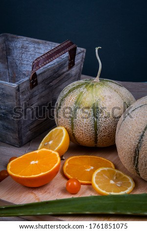 Fruit photography of yummy edible fruits. Honeydew, Chinese lantern fruit, orange, lemon and a leaf of aloe Vera cactus. #1761851075
