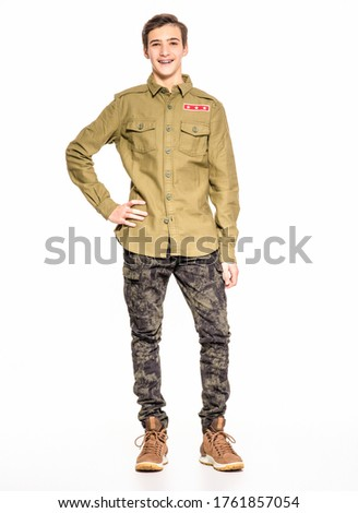 Smiling young man in camouflage clothing. Happy  Conscript in camouflage, isolated. Cheerful rookie in army clothes. Teenager in khaki military clothing poses in a studio on a white background. #1761857054