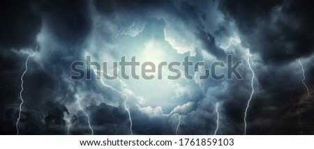 A dark stormy sky with dark clouds and lightning and the sun breaking through the clouds. Concept on the theme of religion, faith, hope, etc. The sun as a symbol of freedom.