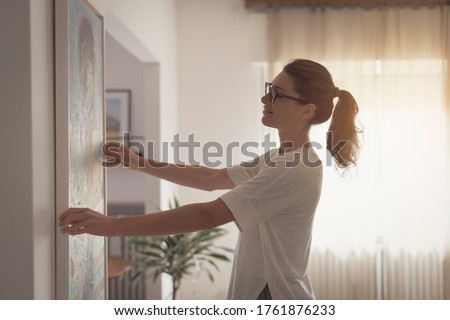 Woman hanging a painting at home and decorating her contemporary living room #1761876233