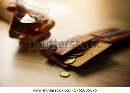 Fired man drinking alcohol for the last money, coins. Wrinkled alcoholic with wallet sits at brown wooden table Royalty-Free Stock Photo #1761885575