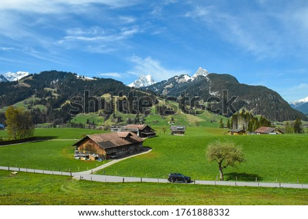 Colorful picture of Swiss village on green grass area with Alps moutain under blue sky, from Golden pass line,  Zweisimmen to Montreux, Switzerland: 7/5/2562
