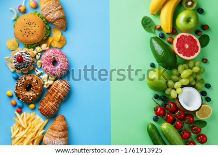 Healthy and unhealthy food background from fruits and vegetables vs fast food, sweets and pastry top view. Diet and detox against calorie and overweight lifestyle concept. Royalty-Free Stock Photo #1761913925