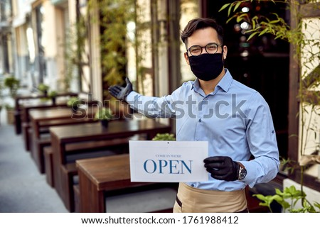 Happy waiter wearing protective face mask and holding open sign while reopening after COVID-19 epidemic.  #1761988412