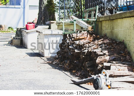 Pile of chopped wood and 2 storage containers for gas cans in front of an old concrete patio at a lake cottage. A gas can and blower are also in the picture