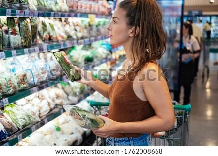 Young smiling woman in local supermarket buying local organic vegetable stock photo