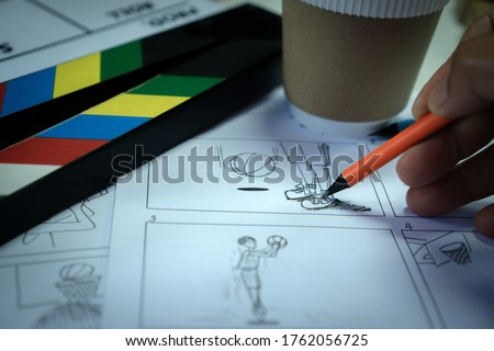 Designer creative drawing in storyboard for film movie, Video Pre-production process in display script production. Design shot scene layout with paper cup coffee and slate in studio.Media product idea