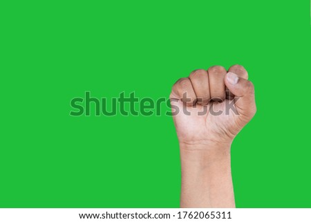 Hand of an Asian man forms Fist isolated on a green screen background.. selective focus
