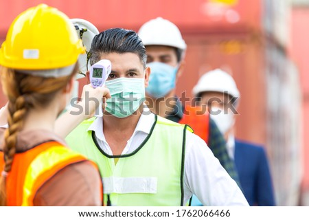 Female worker scanning fever temperature with digital thermometer to construction site staff wearing hygiene face mask protect from Coronavirus or COVID-19. New Normal working life adaptation in 2020 Royalty-Free Stock Photo #1762066466