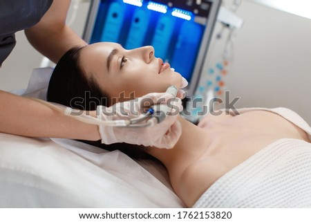Professional female cosmetologist doing hydrafacial procedure in Cosmetology clinic. Royalty-Free Stock Photo #1762153820