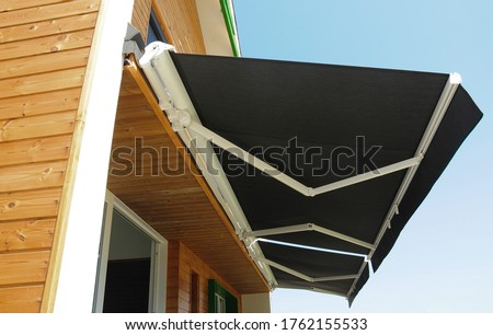 Outdoor high quality automatic sliding canopy retractable roof system, patio awning for sunshade of a modern wooden house.   Royalty-Free Stock Photo #1762155533