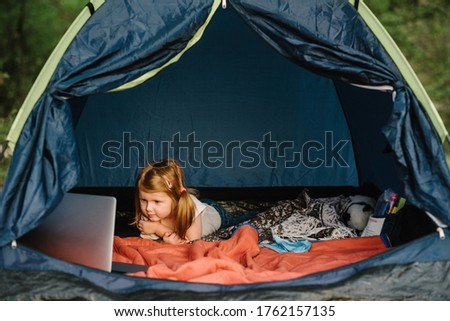 Kid girl in a campaign in a tent. Family summer vacation in nature. Children tourism. Child using laptop in the tent at the campsite. Girl watching cartoon on gadget.