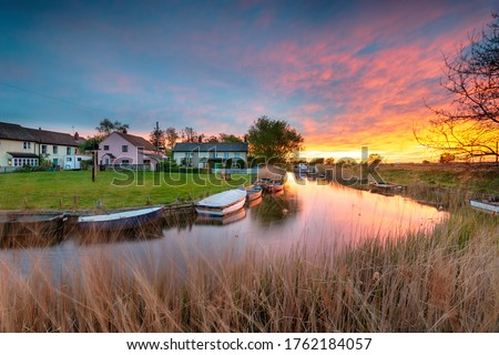 Stunning sunset over the village green and boats on the river at West Somerton in the Norfolk Broads Royalty-Free Stock Photo #1762184057