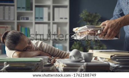 Tired lazy woman sleeping on the office desk, her boss is bringing a pile of paperwork to her desk #1762188749