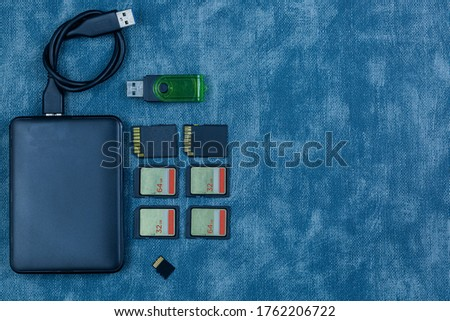 Modern digital devices for the transfer and storage of information. Flash drives, external hard disks and memory cards,Broken hard disk and memory card on the desk.