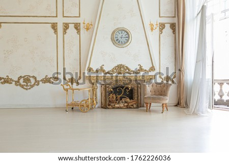 luxurious expensive interior of a large baroque royal living room. antique furniture, gold trim, huge windows, fireplace with gold stucco on the walls. full of daylight Royalty-Free Stock Photo #1762226036