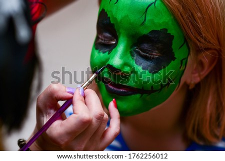 The animator draws green colors on the face of a child.