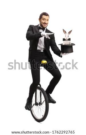 Magician on a unicycle and performing a magic trick with a hat and a rabbit isolated on white background #1762292765