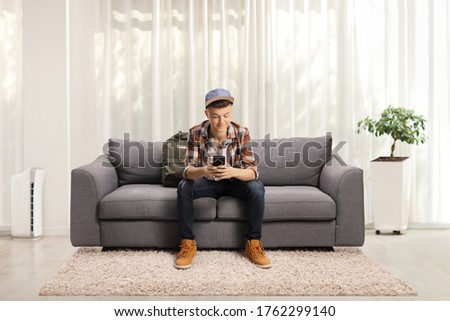 Male student sitting on a sofa with headphones in an apartment  #1762299140