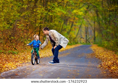 father teaches son to ride the bicycle #176232923
