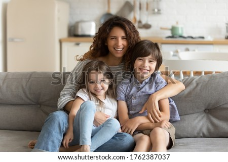 Close up portrait picture of happy young mother with children sitting on couch at home. Smiling parents with little kids hugging looking at camera posing for photo in living room.