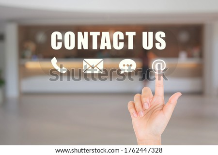 Call Center and Contact US Concept : Hand choosing and pressing on contact us icon symbols with blurry image of luxury hotel lobby reception in the background.