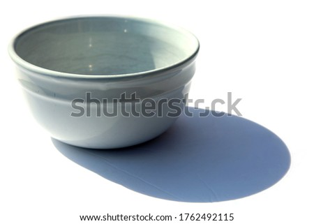 White Bowl. White Ceramic Bowl. Artistic view of a white ceramic bowl with shadows. Isolated on white. Room for text. Clipping Path. Bowls are used world wide for Soups and other liquid ingredients.  #1762492115