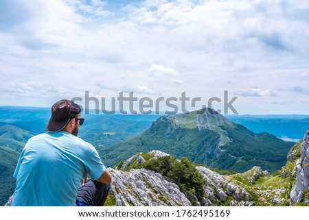 Mount Aizkorri 1523 meters, the highest in Guipuzcoa. Basque Country. Ascent through San Adrian and return through the Oltza fields. A young man in a blue shirt looking at the views from above #1762495169