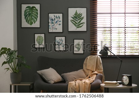 Beautiful artworks and comfortable sofa in stylish room. Interior design Royalty-Free Stock Photo #1762506488