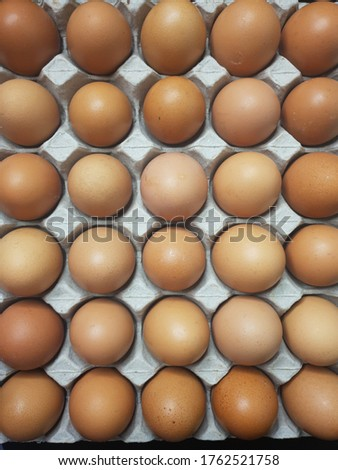 Flat lay Close-up view of raw chicken eggs in egg paper box.Overhead view of brown chicken eggs in an open egg carton.Fresh chicken eggs background. Top view Natural organic egg. healthy real food. #1762521758