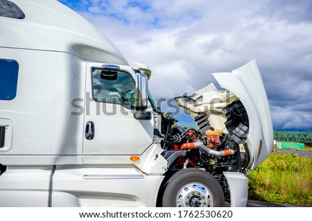 Broken Big rig industrial professional white semi truck with open hood and long haul semi trailer standing on the road shoulder trying to fix breakdown in place and waiting for road repair assistant Royalty-Free Stock Photo #1762530620