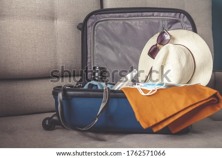 Travel. masked girl puts her things in a suitcase and dreams of rest, traveling after quarantine, blocking, covert 19. Staycation.local travel.Tourism after opening borders, end of quarantine #1762571066