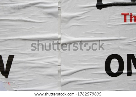 Old peeling white street poster with typography letters