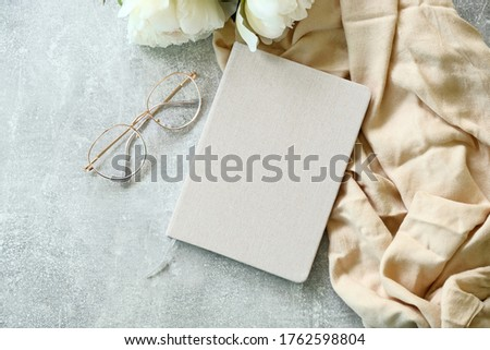 Flat lay paper notebook, eyeglasses, peony flowers and beige cloth on stone background. Top view girl home office desk with elegant accessories. Modern feminine workspace concept Royalty-Free Stock Photo #1762598804